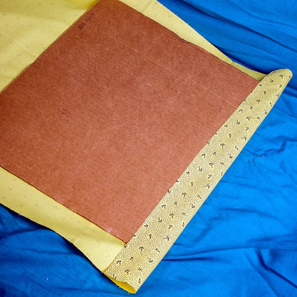 line up fabric to back of cardboard and staple on